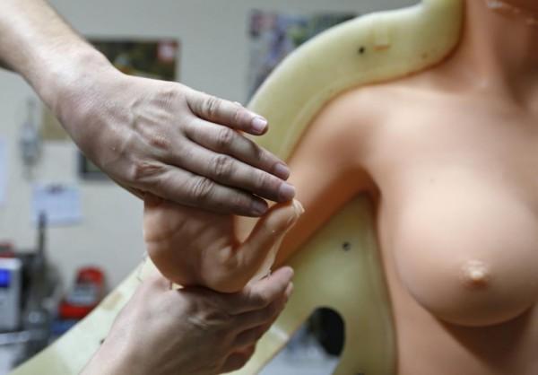 Эрик, сотрудник Dreamdoll, достает куклу из формы, проверяет ее гибкость.