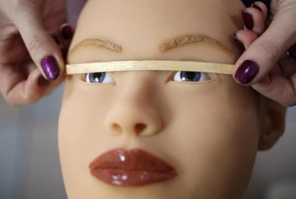 Рафаэла проверяет, ровно ли расположены глаза куклы.